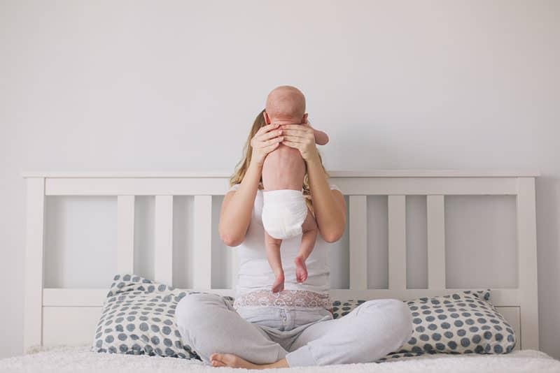Mutter hält ihr Baby auf dem Bett