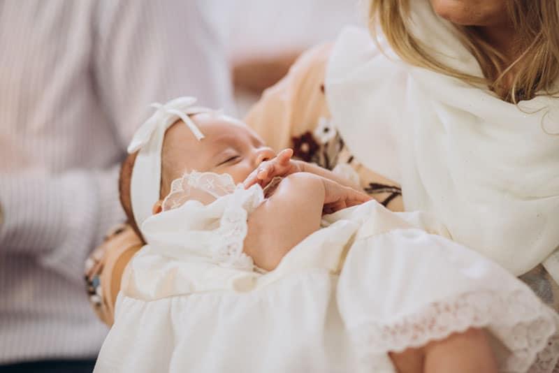 Mutter hält ihr Baby zur Taufe