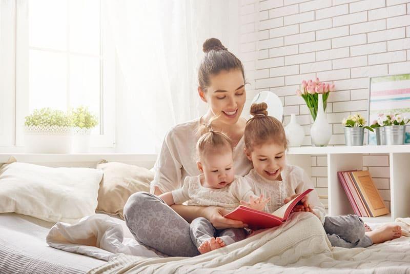Mutter mit Babys, die ein Buch lesen
