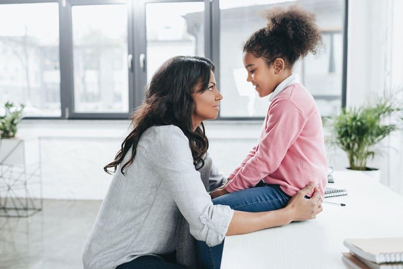 Mutter spricht mit ihrer Tochter in der Küche