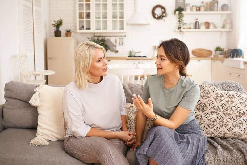 Mutter und Tochter sitzen am Sofa und reden