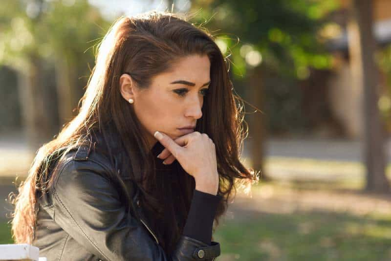 Nachdenkliche Frau, die allein draußen sitzt