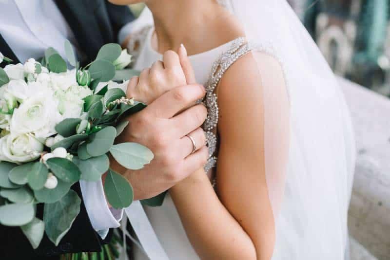 Nahaufnahme der Hand des Bräutigams, die das Handgelenk der Braut zart hält