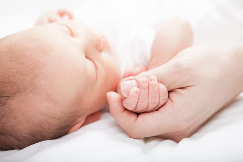 Neugeborenes hält den Daumen ihrer Mutter