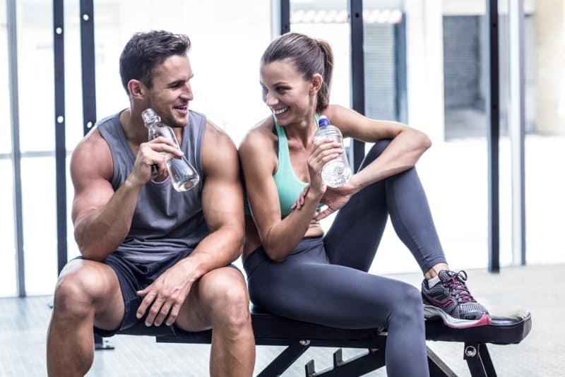 Paar Trinkwasser und sitzen im Fitnessstudio