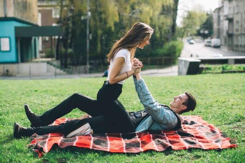 Paar, das gute Zeit im Garten auf Decke hat