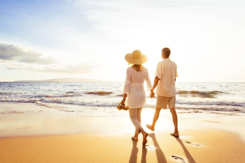 Paar hält ihre Hände beim Gehen am Strand