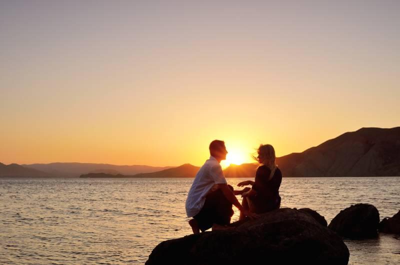 Paar sitzt am Meer auf Sonnenuntergang