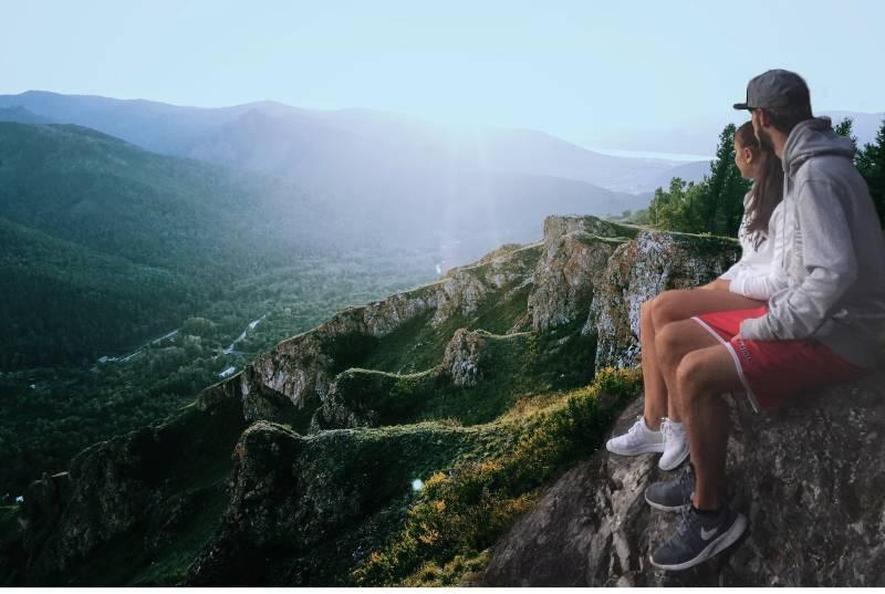 Paar sitzt am Rand beim Blick auf die Berge