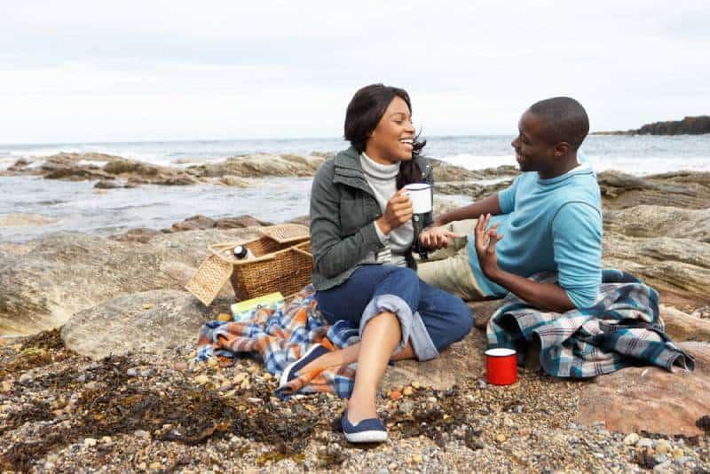 Paar sitzt am See und redet