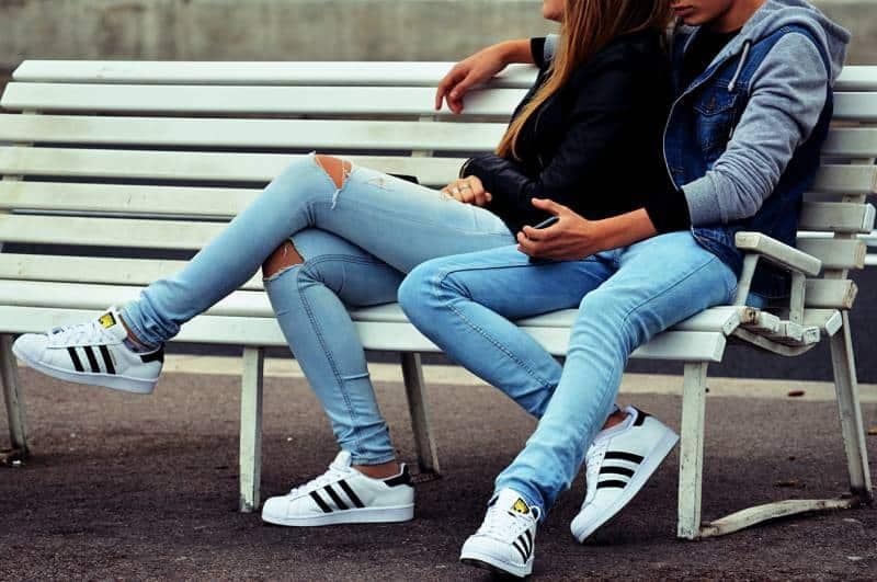 Paar sitzt an der weißen Bank