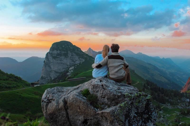 Paar sitzt auf dem Hügel