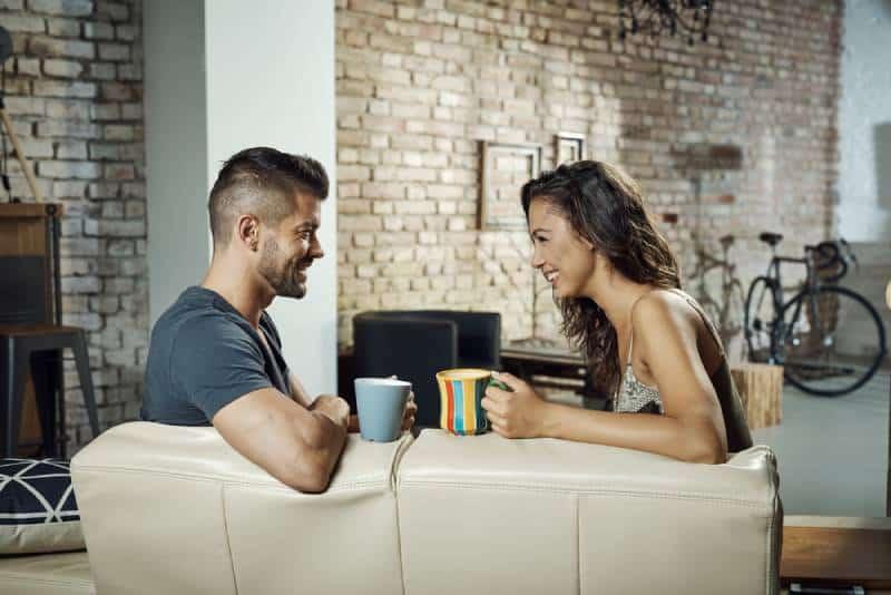 Paar sitzt im Wohnzimmer und spricht mit Kaffee