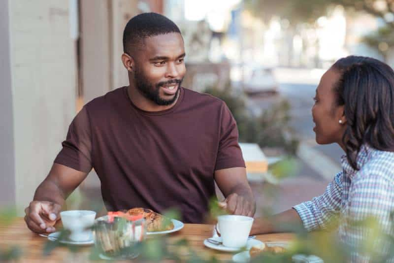 Paar spricht außerhalb des Cafés