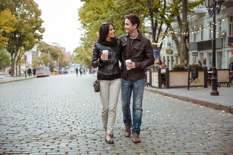 Paar trinkt Kaffee beim Gehen