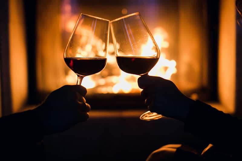 Paar trinkt Wein vor dem Kamin