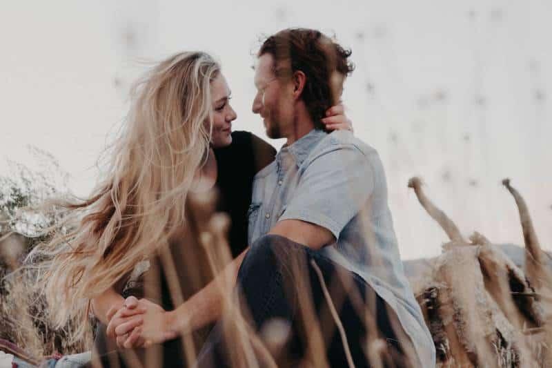 Paar umarmt sich, während es seine Hände hält