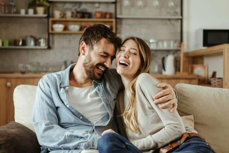 Paar umarmt und lächelt im Wohnzimmer