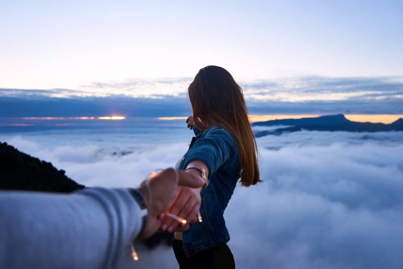 Person, die Frauenhand oben auf Hügel hält