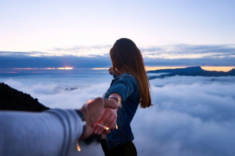 Person-die-Frauenhand-oben-auf-Hügel-hält