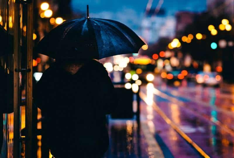 Person, die auf Straße geht, während schwarzer Regenschirm hält