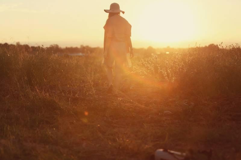 Person, die auf grünem Gras während des Sonnenuntergangs steht