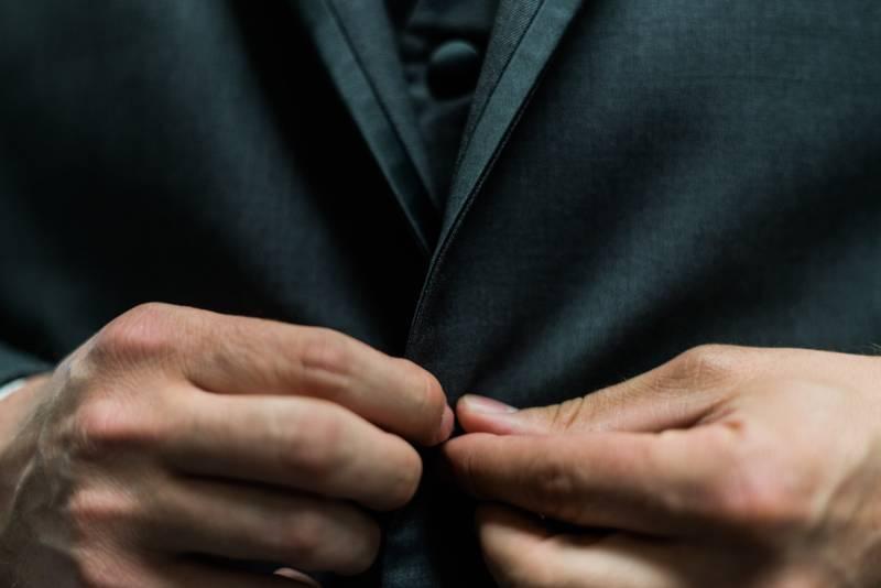 Person mit schwarzem Anzug Jackenknopf