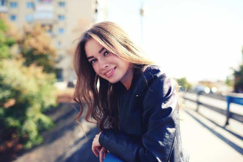 Porträt der glücklichen lächelnden Frau, die auf dem Platz steht
