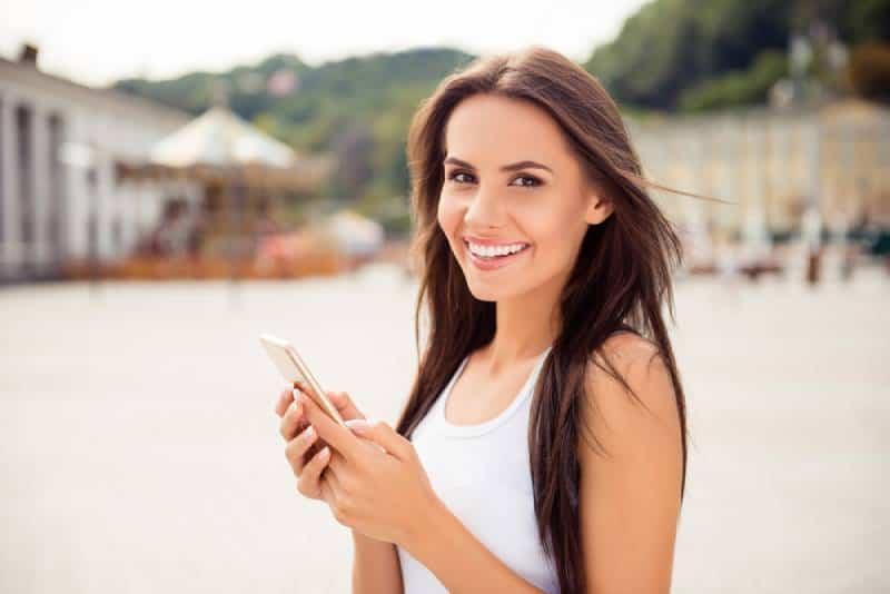 Porträt der lächelnden Frau, die auf ihrem Telefon tippt