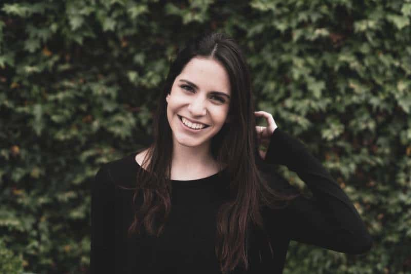 Porträt der lächelnden Frau, die schwarzes Hemd trägt