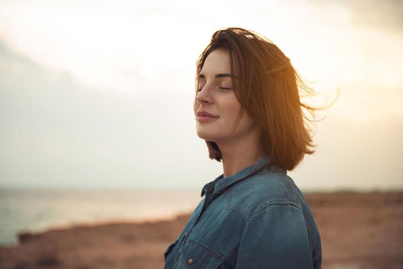 Porträt des lächelnden Mädchens, das am Meer steht