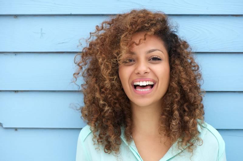 Porträt einer fröhlichen jungen afrikanischen Frau lächelnd