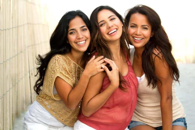 Porträt von hispanischen Freunden, die am Strand lächeln.