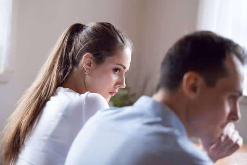 Rückansicht der beleidigten Frau, die hartnäckigen Liebhaber betrachtet