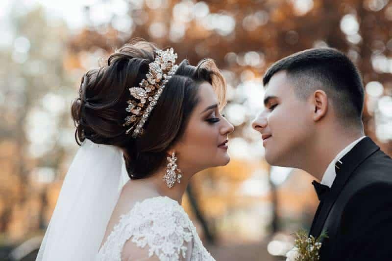 Sanfte Berührung des Bräutigams mit der Braut, gehen Sie in den Park
