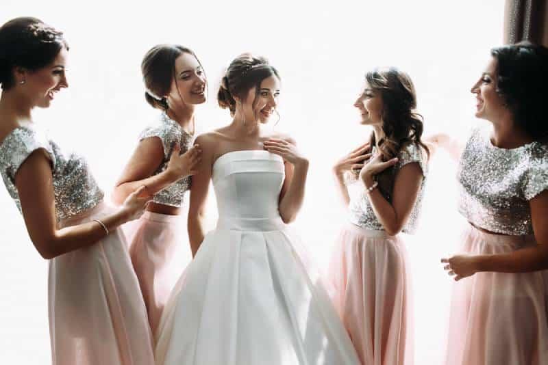 Schöne Braut u. Brautjungfern, die nahe Fenster, Hochzeitsvorbereitung aufwerfen