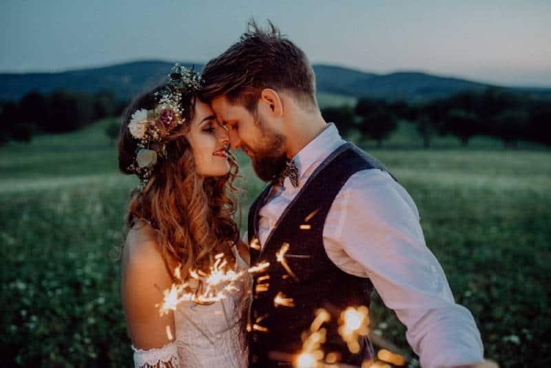Schöne Braut und Bräutigam mit Wunderkerzen auf einer Wiese.