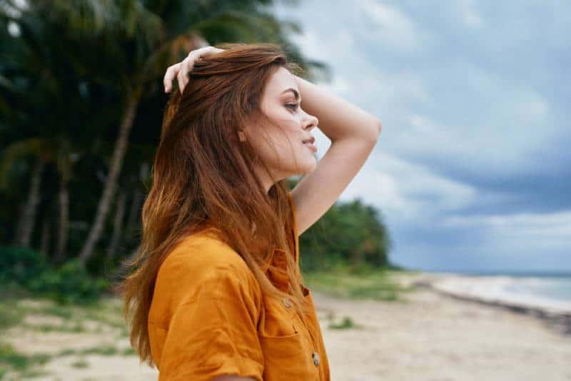 Schöne Frau des roten Haares in einem gelben Sommerkleid auf der Insel