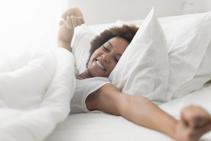 Schöne Frau wacht in ihrem Bett auf, sie lächelt und streckt sich