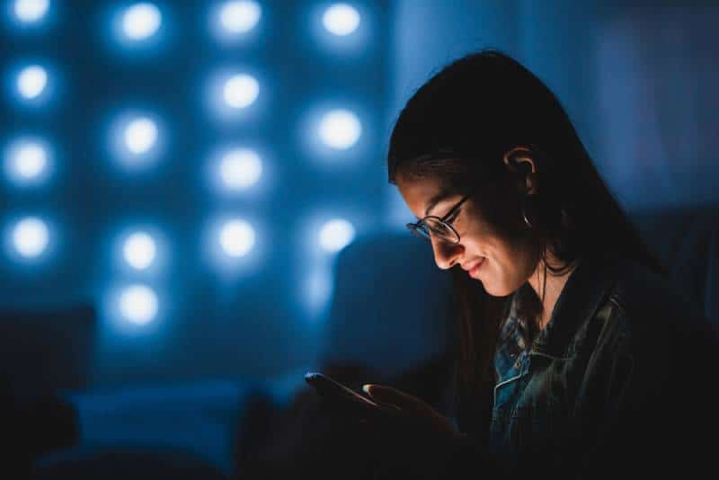 Schöne junge Frau Teenager lächelnd mit ihrem Smartphone