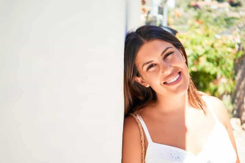 Schönes Mädchen, das sich auf weiße Wand stützt, hing freundliche Frau, die glücklich an einem sonnigen Tag des Sommers lächelt