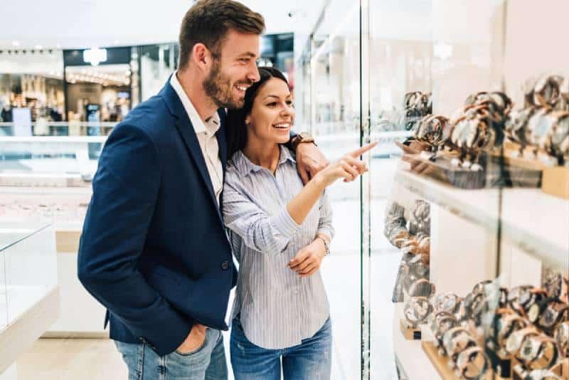 Schönes Paar, das beim Einkaufen im modernen Juweliergeschäft genießt.