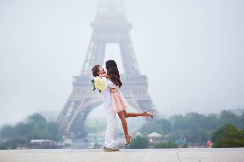 Schönes romantisches Paar verliebt in Bündel der weißen Rosen