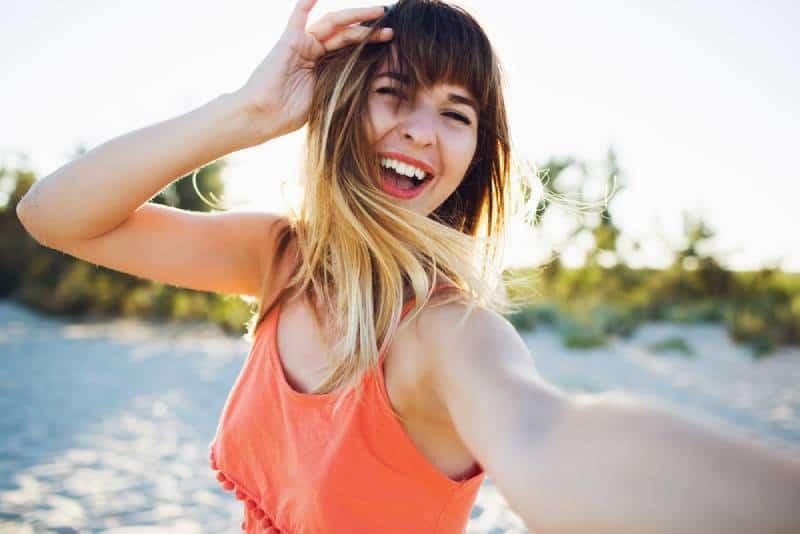 Schließen Sie herauf Porträt der glücklichen lachenden Frau am Strand