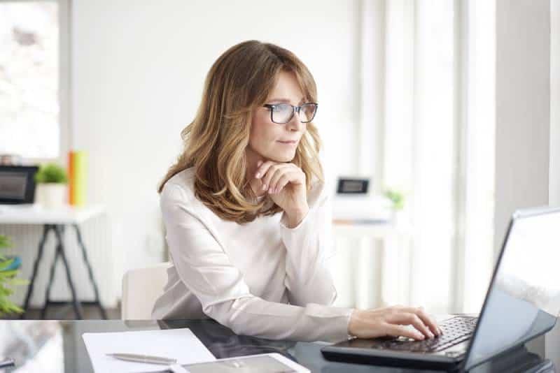 Schuss einer attraktiven reifen Geschäftsfrau, die am Laptop arbeitet