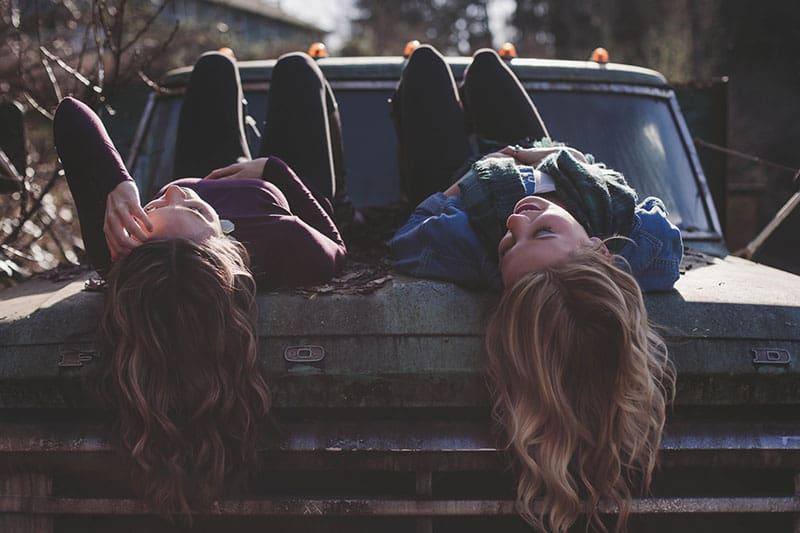 Schwestern, die auf dem alten Auto liegen