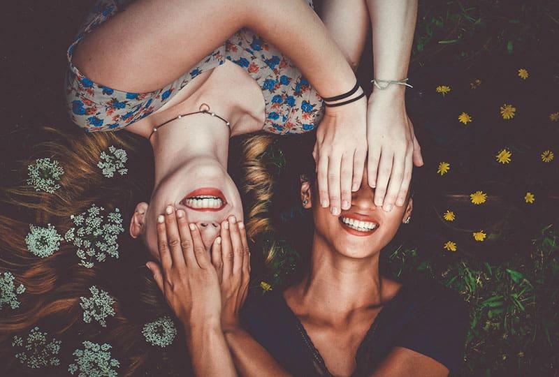 Schwestern, die in Blumen mit den Händen auf den Augen liegen