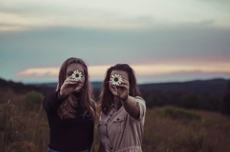 Schwestern halten eine Blume auf dem Feld