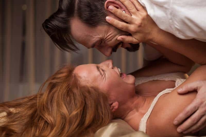 Seitenansicht des aufgeregten Mannes liegt über Frau im Bett.