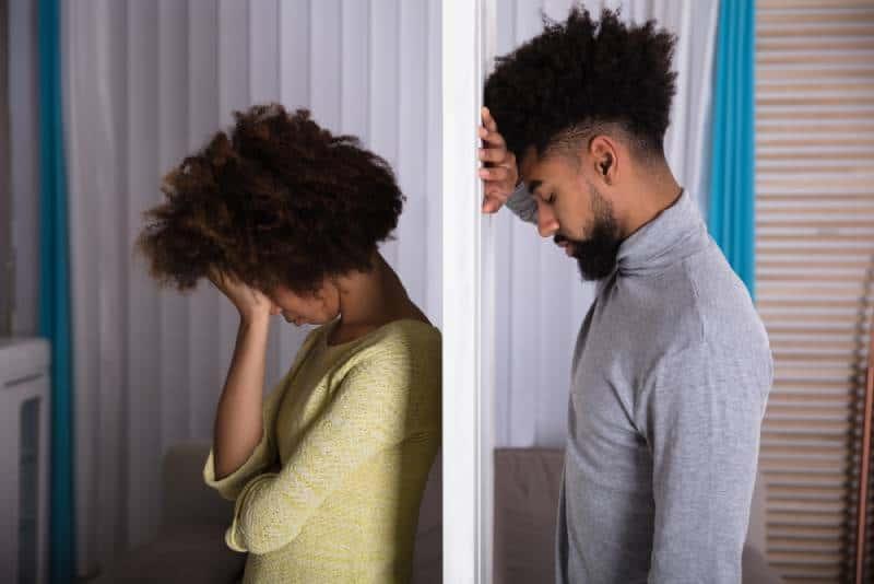 Seitenansicht des jungen unglücklichen Paares, das Rücken an Rücken zu Hause steht
